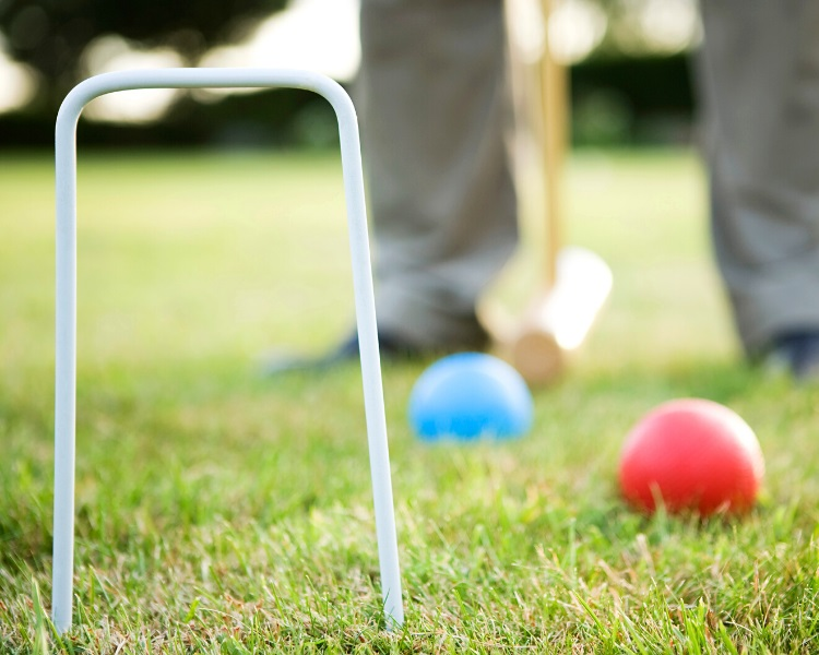 Playing a game of croquet outside